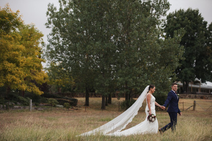 bride and groom walking in paddock with veil trailing country wedding de lumiere photography
