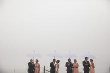 Bridal party in the rain holding umbrellas - de lumière photography