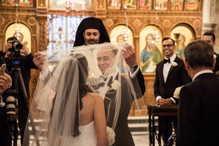 groom lifting the brides veil at the altar