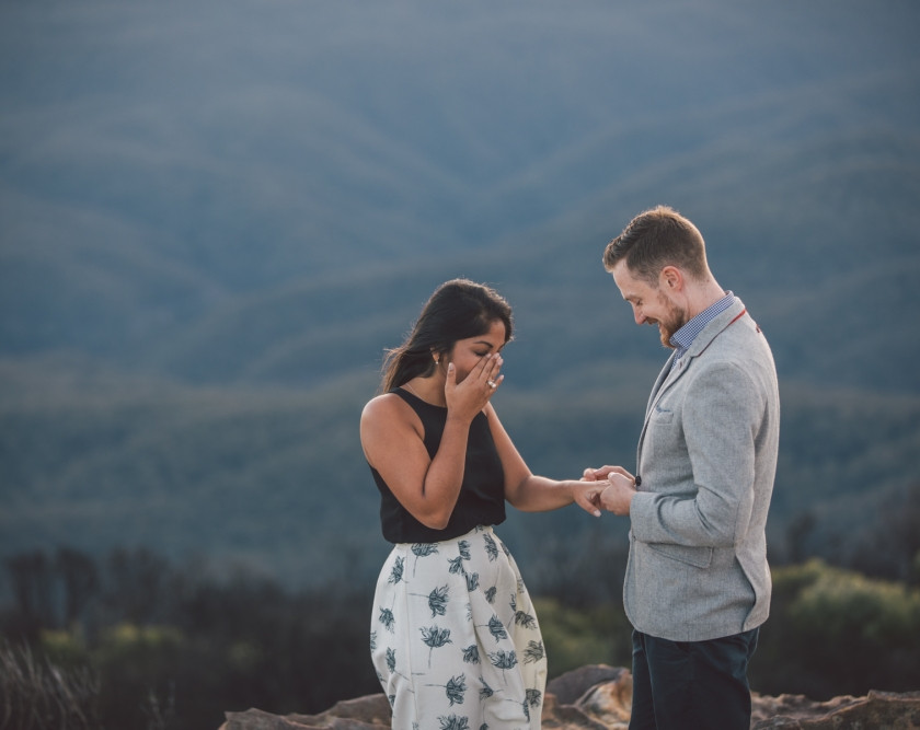 Woman cries as man puts engagement ring on her finger