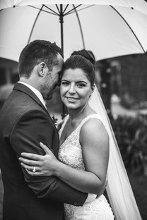 Black and white portrait of bride and groom under an umbrella - de lumière photography