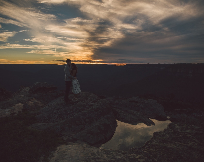Sunset reflected in puddle with couple hugging