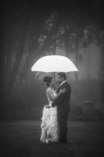 Bride and groom on their rainy wedding day under an umbrella - de lumière photography