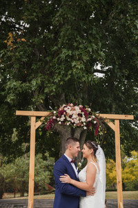 bride and groom under floral arch country wedding de lumiere photography