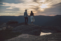 Woman and man standing on rock looking at sunset