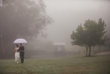 Bride and groom walk under an umbrella through the grounds of Suzarosa - de lumière photography