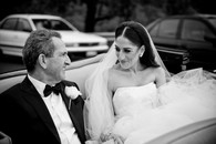 father and daughter smiling in wedding car