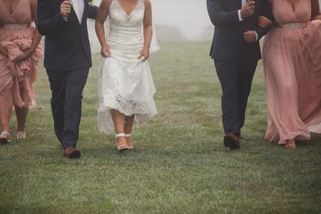 Bridal party walking over wet grass - de lumière photography