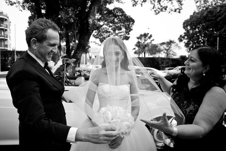 mother and father preparing bride to walk down aisle