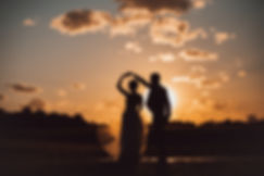 bride and groom dancing in a country sunset