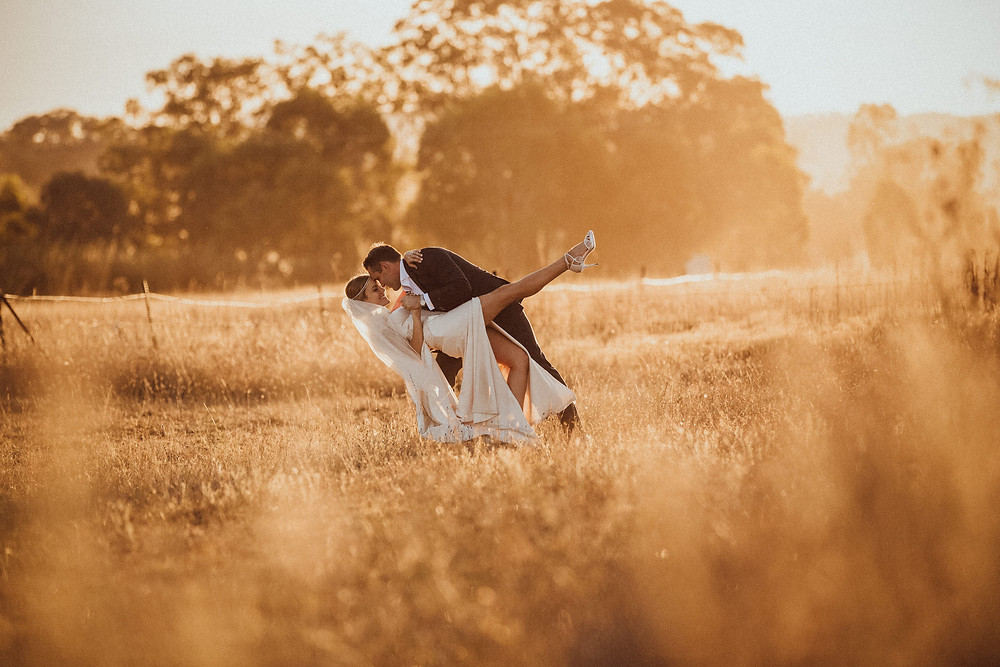 groom dipping bride while dancing in gorgeous golden light