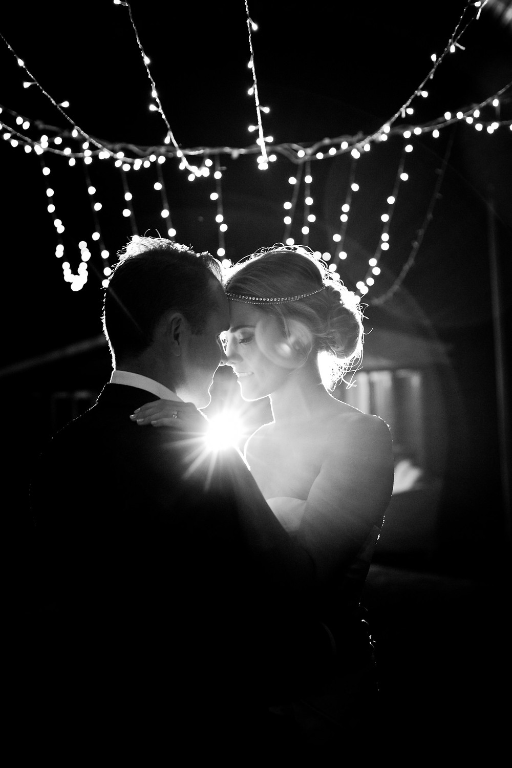bride and groom dancing under fairylights at country wedding