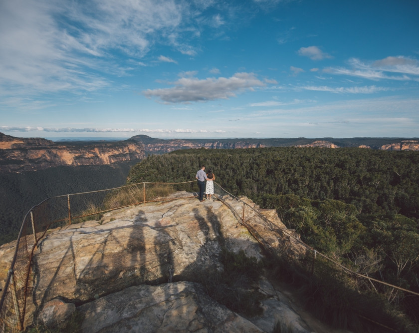 Couple and shadows looking over blue mountains