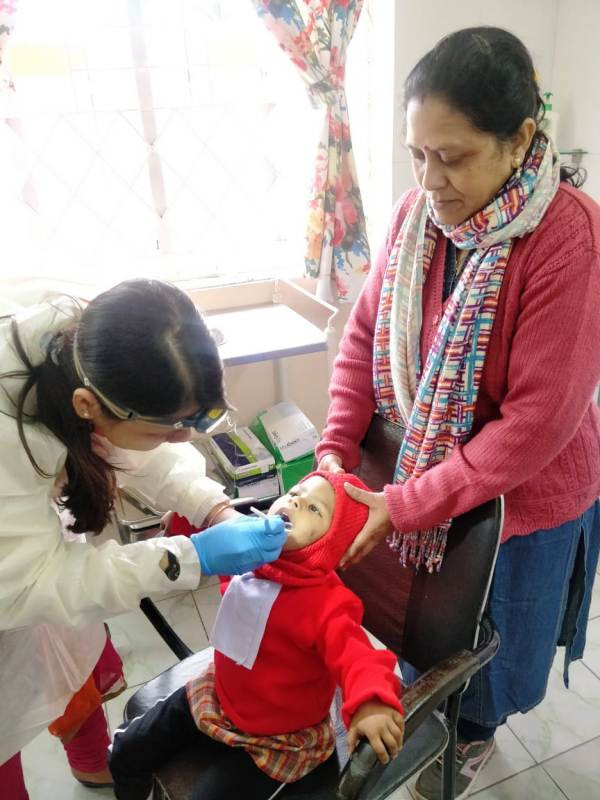 Special Educator Sumitra is holding tiny Kritanjali, while Dr. Agarwal is treating the child.
