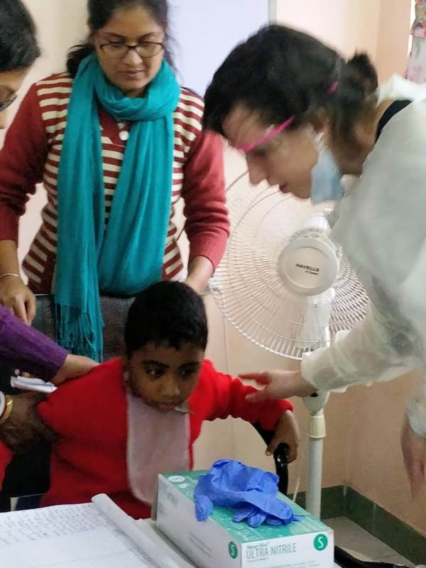Dr. Elise Sarvas checking Special child,   Adarsh's teeth. Special Educator Subhra Pal is holding the child
