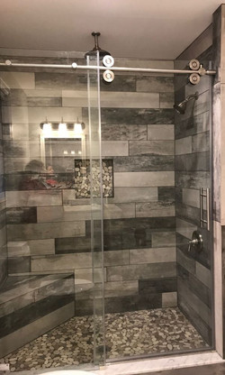 grey walk in shower with bench
