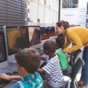 teacher-teaching-schoolgirl-in-computer-