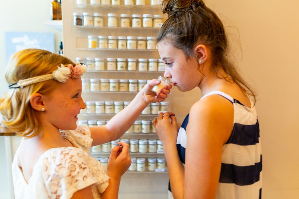Two young girls smelling candle from scent wall