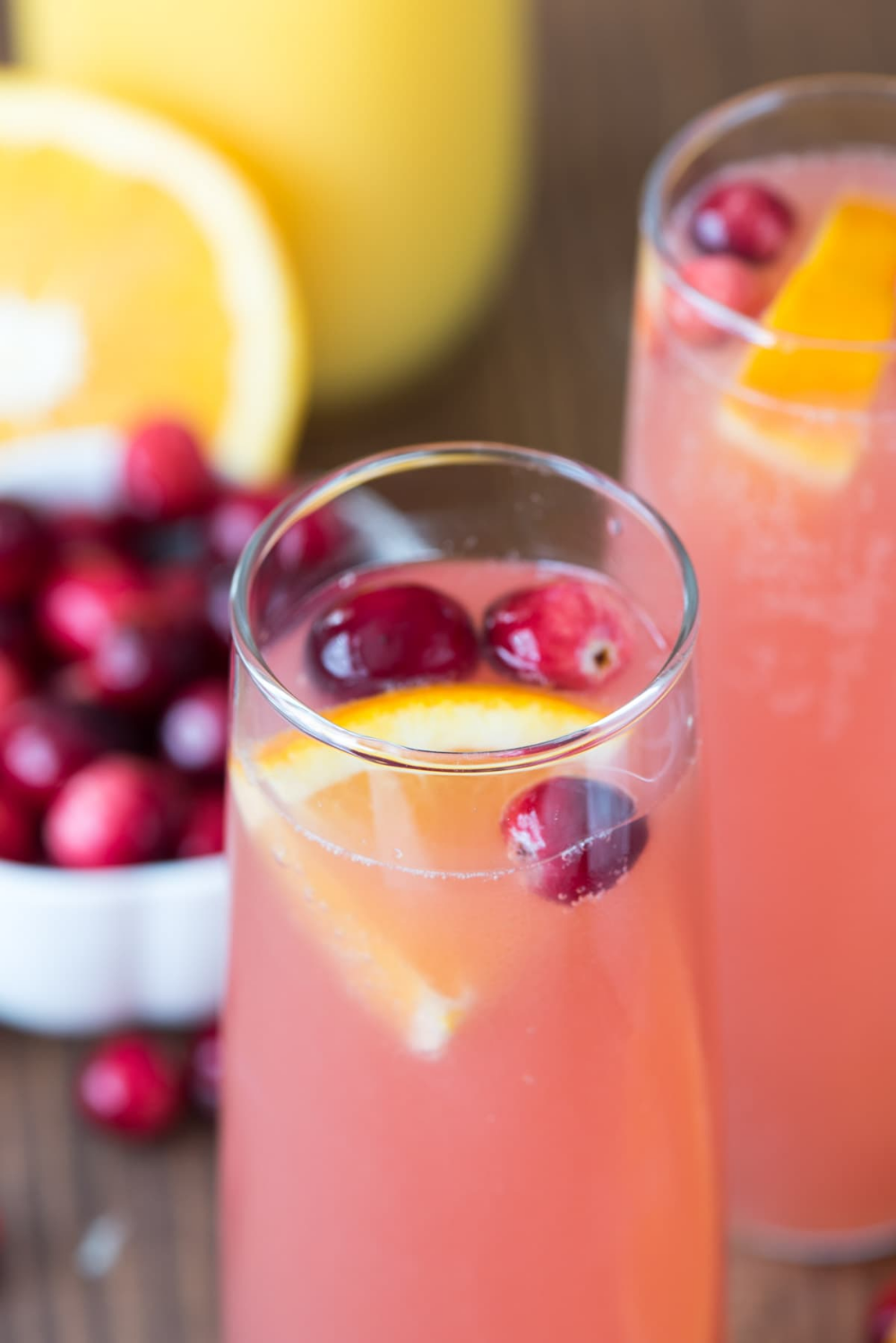 Pink Mimosa with cranberry and orange garnish