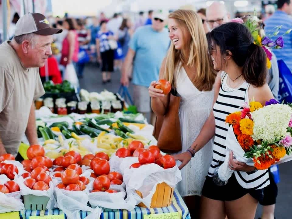 Two girls laughing while talking to a local produce vendor