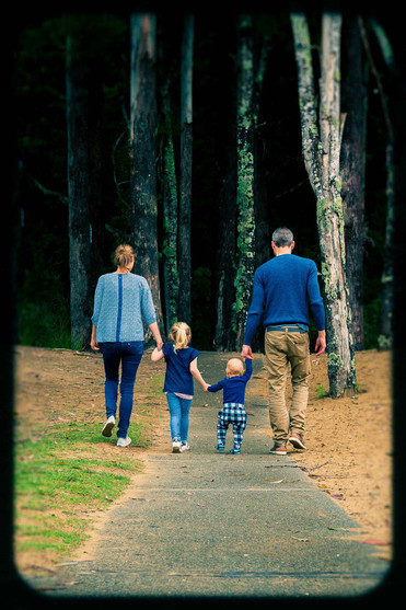 family wearing blue walk in the trees in