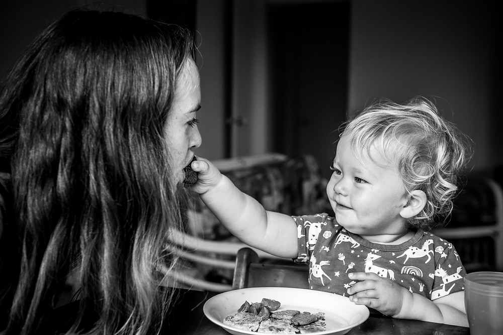 Black & white image of mum being fed a strawberry by documentary family photographer Josie Gritten