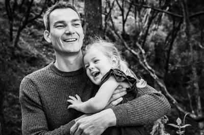 dad and daughter have joyful cuddle blac