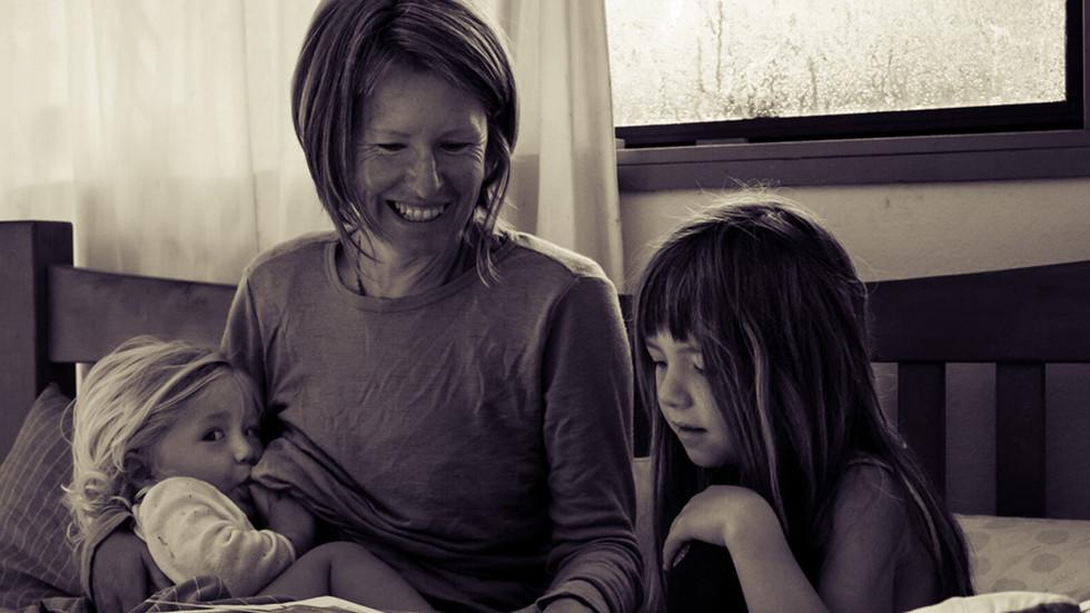 mum-breastfeeds-reads-in-bed-josie-gritt