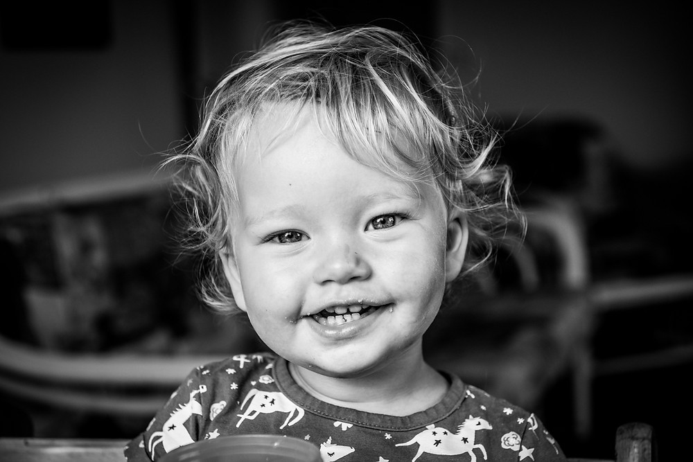 black & white image of girl grinning at camera Black & white image of mum looking lovingly at daughter by documentary family photographer Josie Gritten