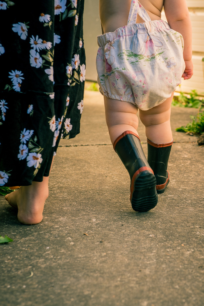 Colour close up image of mum & toddler walking iconic Kiwi scene with Red bands Black & white image of mum looking lovingly at daughter by documentary family photographer Josie Gritten