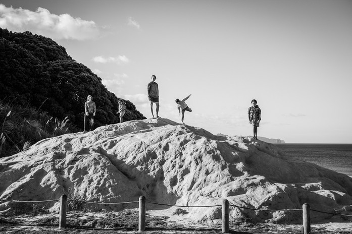 Kids stand on a rock by the beach by family photographer Josie Gritten