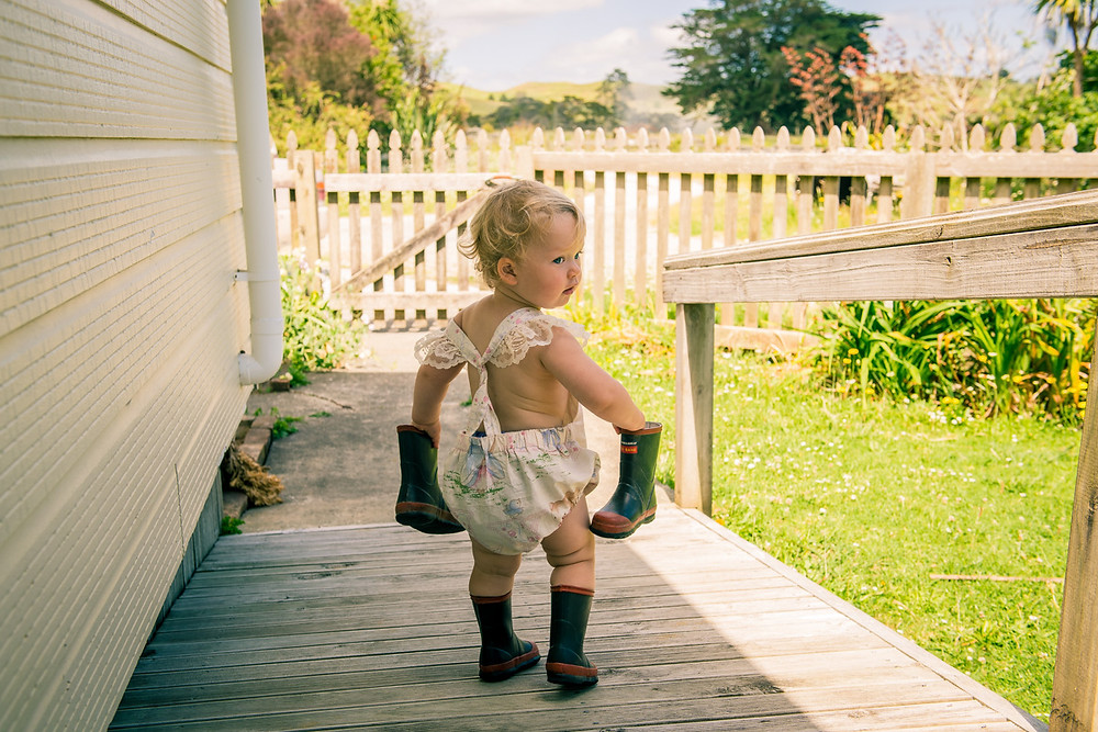 little girl outside in New Zealand wearing RedBand gumboots Black & white image of mum looking lovingly at daughter by documentary family photographer Josie Gritten