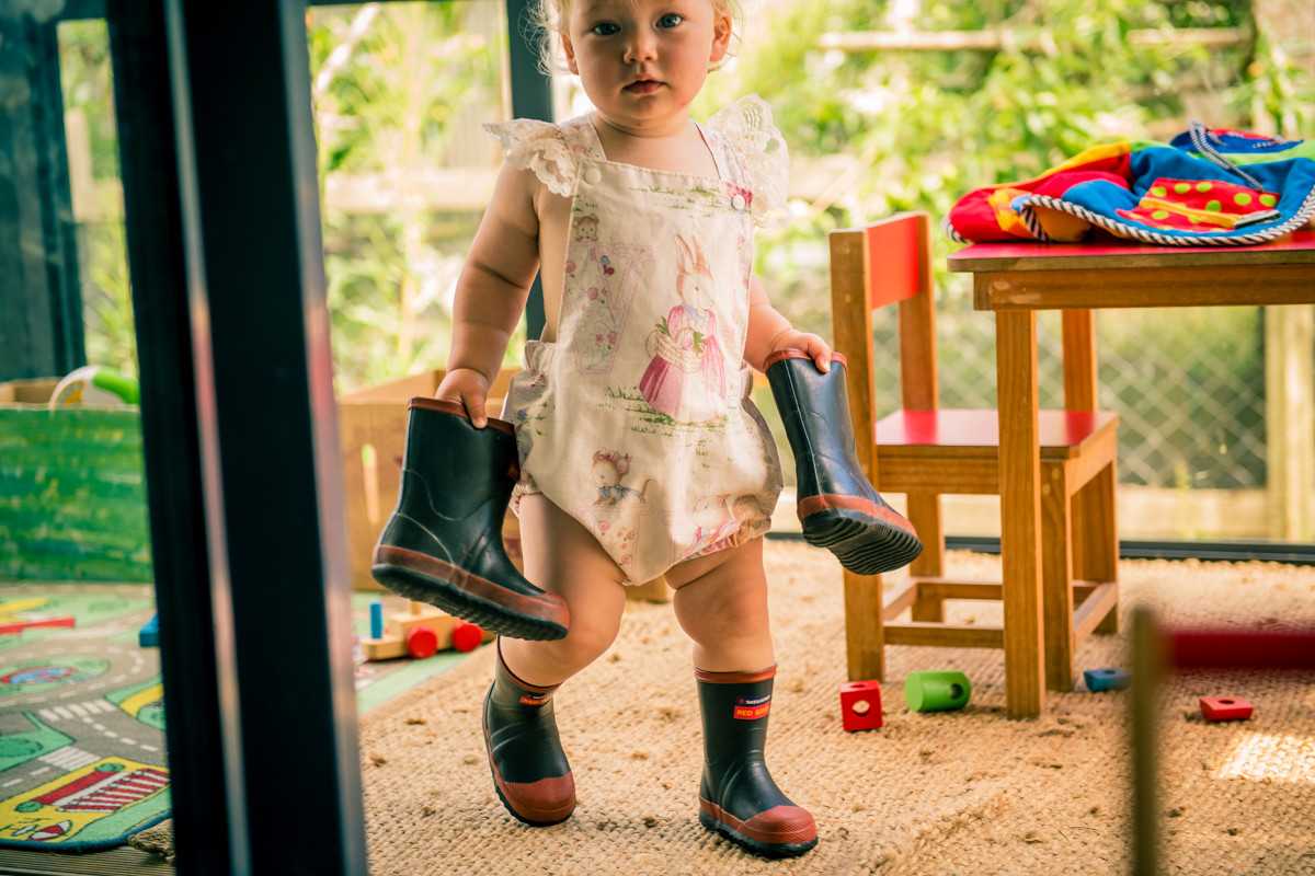 In the doorway with gumboots