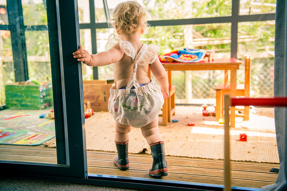 little girl in doorway wearing Red Band gumboots Black & white image of mum looking lovingly at daughter by documentary family photographer Josie Gritten
