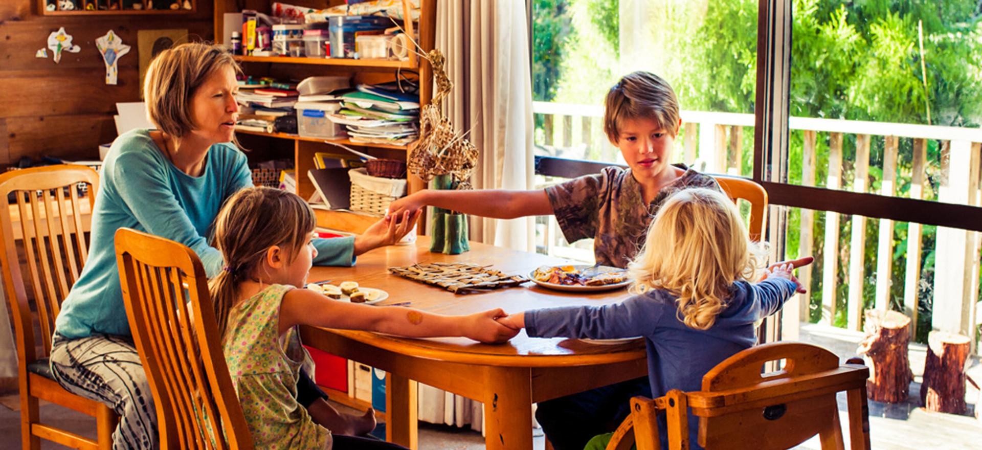 family-sits-around-table-karakia-josie-g