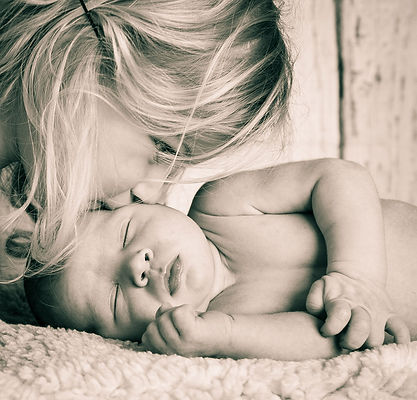 Black & white image of toddler kissing her newborn brother by family photographer Josie Gritten