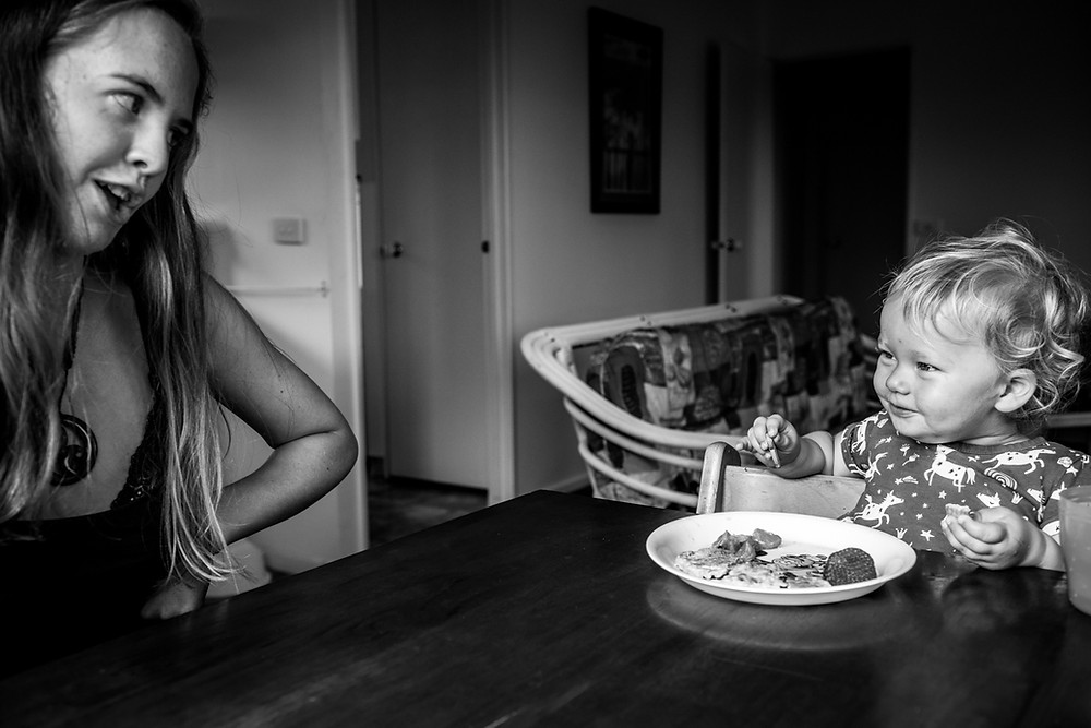 black & white image of mum and daughter by table Black & white image of mum looking lovingly at daughter by documentary family photographer Josie Gritten