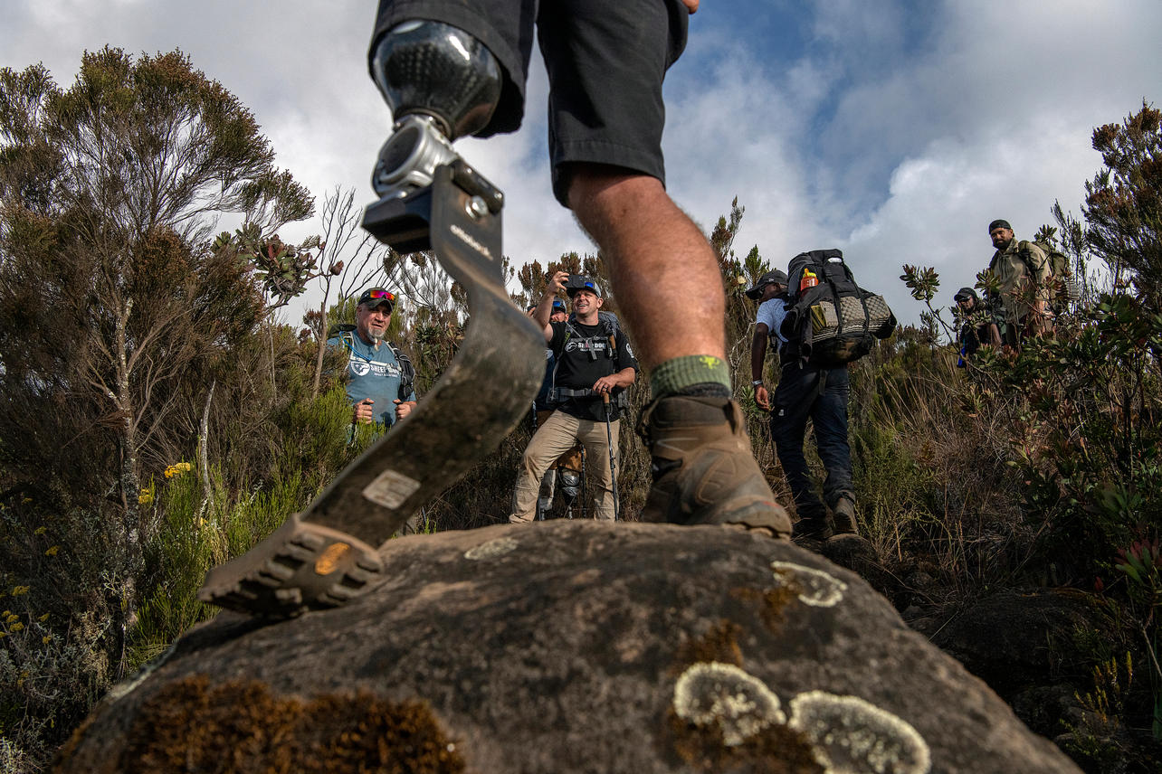 Noah Galloway stands on a rock as Michael Nimmo takes a picture of him on August 5, 2021 during day two of the eight-day climb to summit Mount Kilimanjaro.