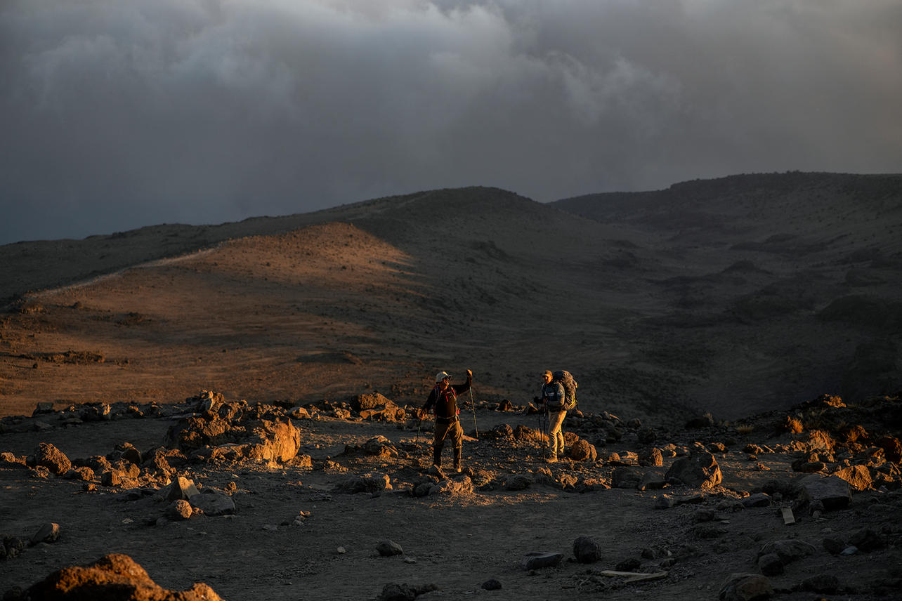 """Chris """"Yeti"""" Jackson and Michael Nimmo take in the setting sun right before hitting Barafu Camp (base camp) on August 8, 2021 during day five of an eight-day climb to summit Mount Kilimanjaro."""