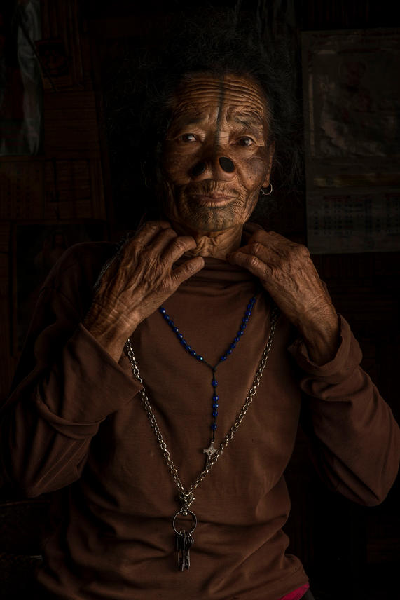 """Tilling Riniyo, 70. She lives in Hong Village, Ziro, India.  At 10 or 11 yrs old Riniyo had her modifications done. She tried to run away but was caught and her hands and feet were tied up. Riniyo says, """" I moved a lot when they were tattooing me and my tattoos are not perfect. I get a little bit jealous of others straight tattoos. I wish I could of borne the pain so my lines would be straight""""."""