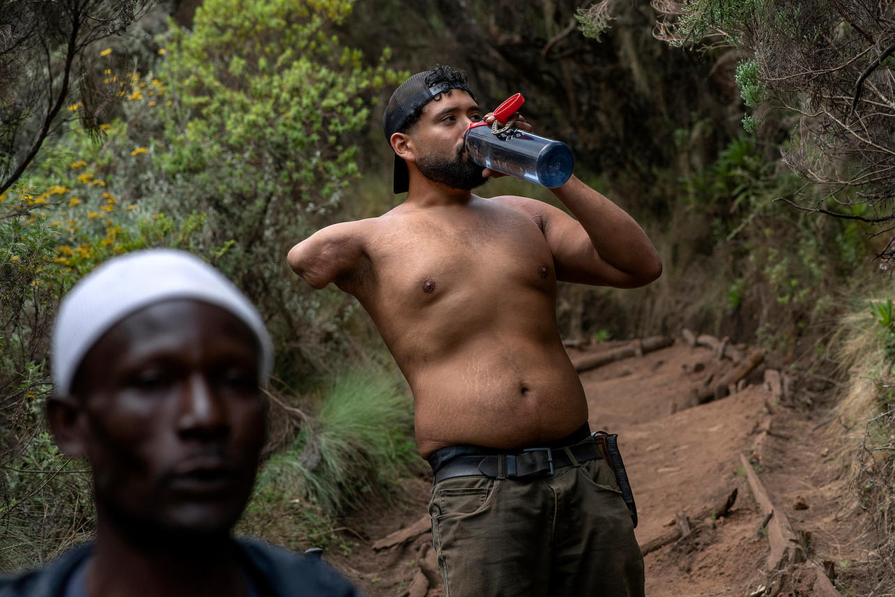 Sebastian Gallegos stops to take a drink of water on August 5, 2021 during his trek to summit Mount Kilimanjaro. Day two of the trek, the group will reach an altitude of 11,500 ft coming out of the rain forest and into savannah tall grasses, heather and volcanic rock draped with lichen beards.