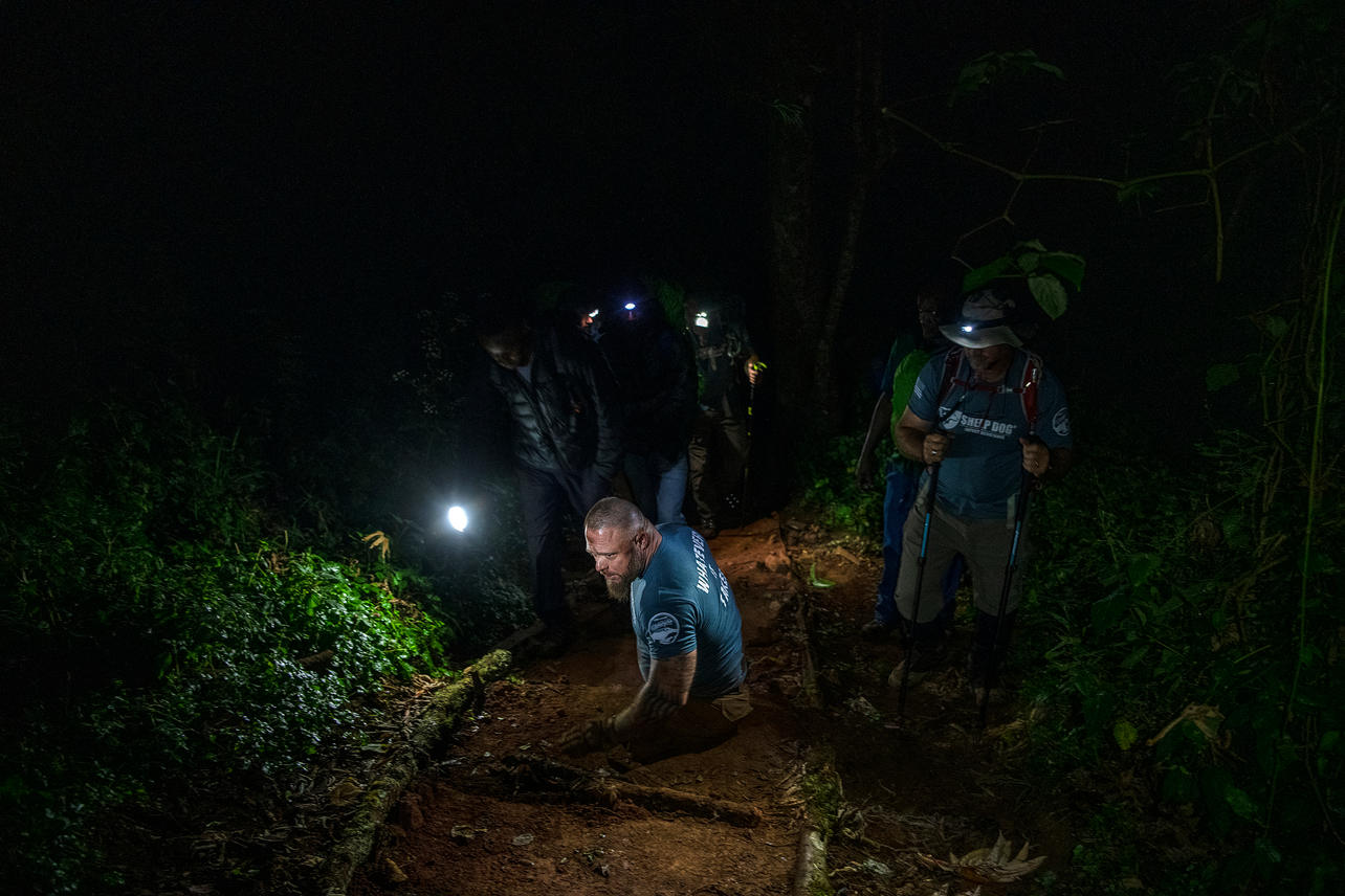 Guided by headlamps, Travis Strong treks through the rain forest on his hands and butt on August 4, 2021. It takes Travis almost triple the time to move the same distance as an able person in this rough terrain.