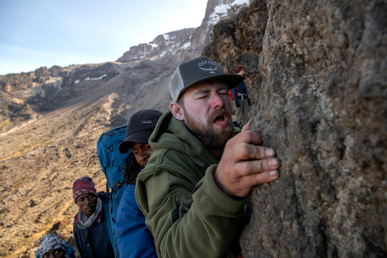 """Scott West navigates around the Great Barranco Wall, """"Kissing Rock"""" on August 8, 2021 during day five of an eight-day climb to summit Mount Kilimanjaro. Kissing Rock is near the top of the wall where the path narrows and you have to hold onto the rock to move on safely."""