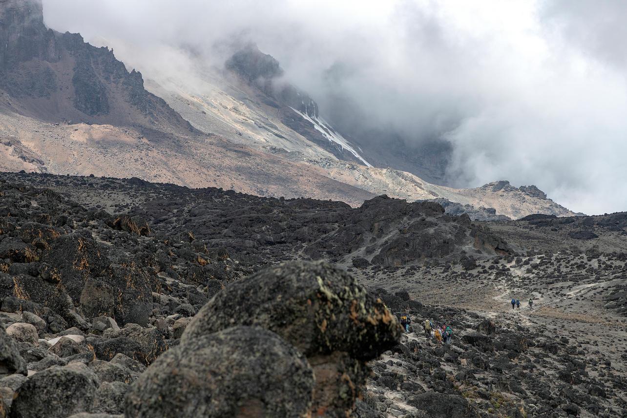 KCC team members trek through Kilimanjaro's alpine desert on August 7, 2021 during day four of an eight-day climb to summit Mount Kilimanjaro.