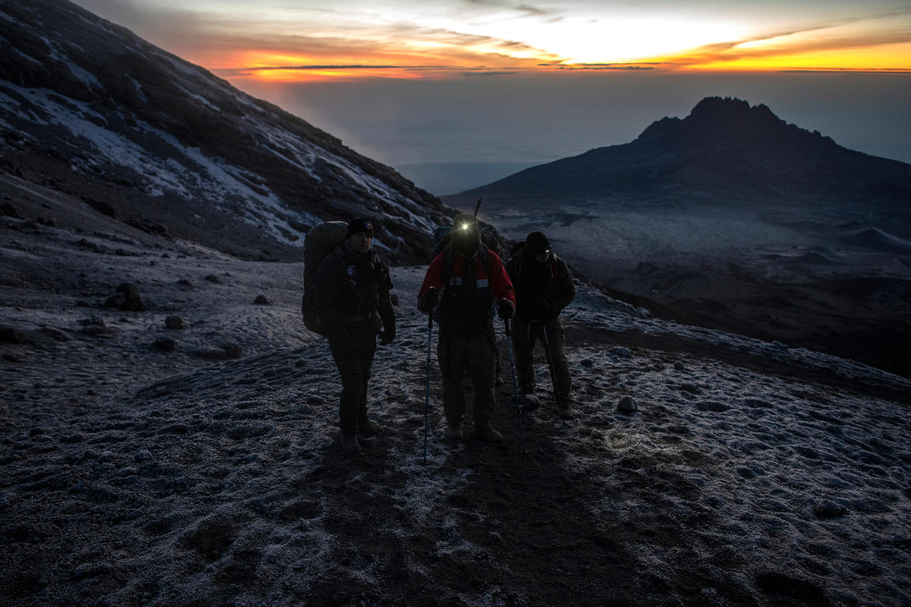 """As the sun rises on Uhuru Peak and six hours of climbing through the night, Anthony """"Brandon"""" Matteson (C), Michael Nimmo (L) and Chris """"Yeti"""" Jackson (R) are near to Stella Point (18,900 ft) on August 10, 2021 during day seven of an eight-day climb to summit Mount Kilimanjaro."""