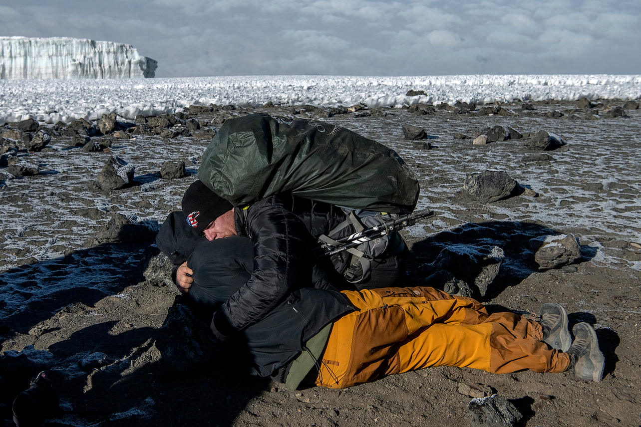 Michael Nimmo gives Scott West a congratulations hug on the summit of Mount Kilimanjaro on August 10, 2021 during day seven of an eight-day climb to summit Mount Kilimanjaro.