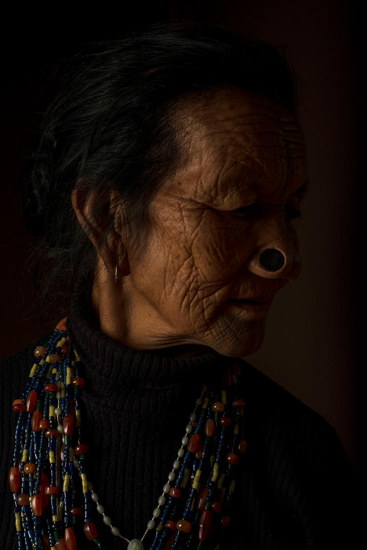 "Michi Yaring, 75-80. She lives in Hong Village, Ziro, India.  Yaring was 14 yrs old when she had her nose done and was tattooed at 15 yrs old. When her mother started to tattoo her she screamed a lot and asked to wait until her father came home from the jungle. Yaring said, ""Five people including her father had to catch her and hold her down"". Although it was very painful, she would like the younger girls to take on the responsibility and continue the tradition."