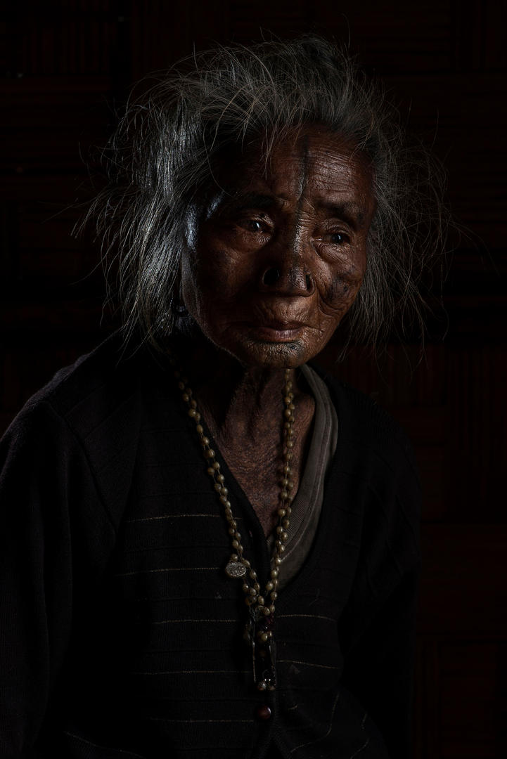 "Kago Yapii, 70's. She lives in Hong Village, Ziro, India.  When Yapii was five or six she had her modifications done. She says, ""I really wanted to have this done and I had no fear at all""."