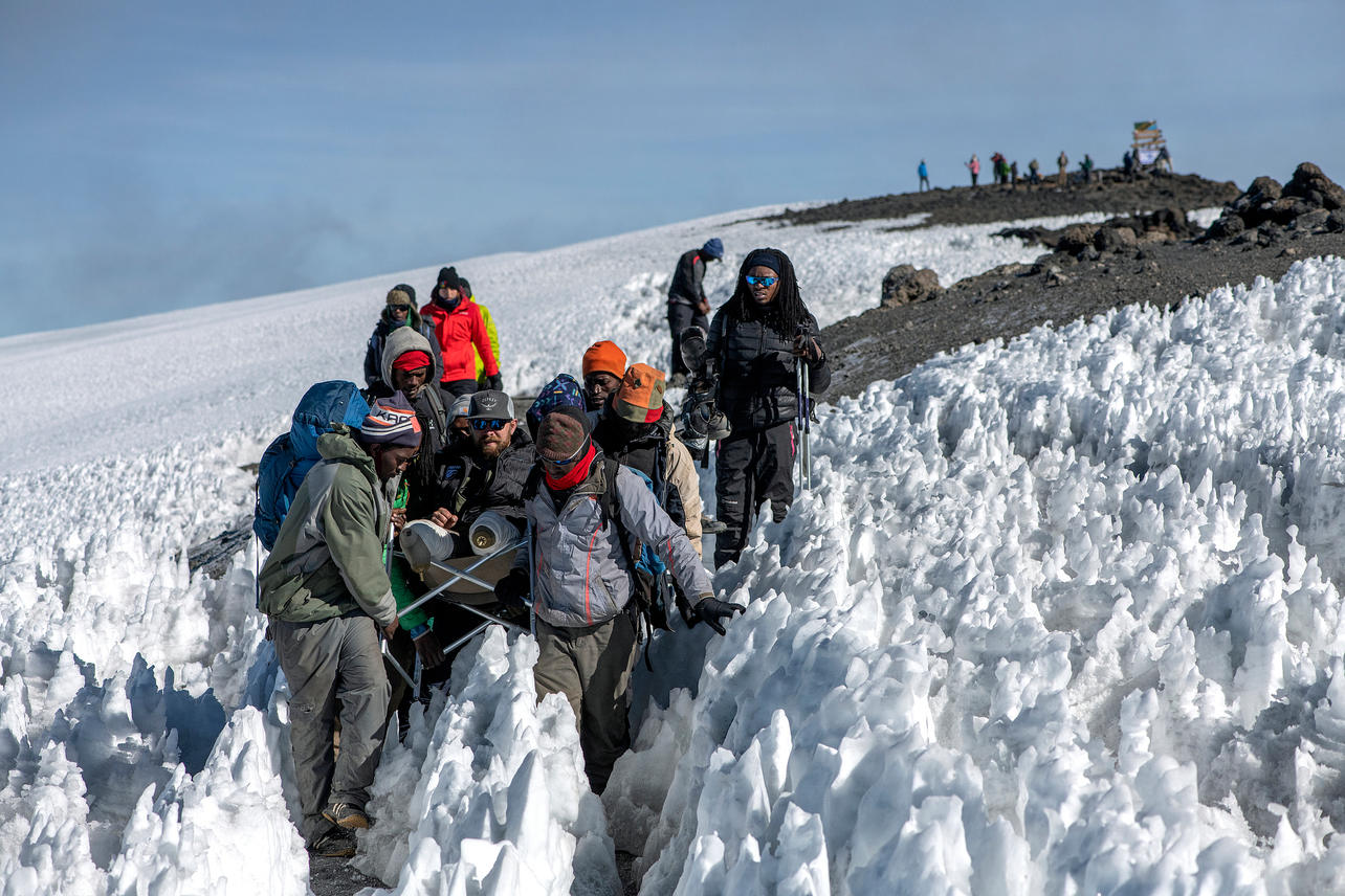 After reaching Uhuru Peak, the summit of Mount Kilimanjaro and with his prosthetic legs off, Scott West is helped down the mountain by guides on August 10, 2021 during day seven of an eight-day climb to summit Mount Kilimanjaro.