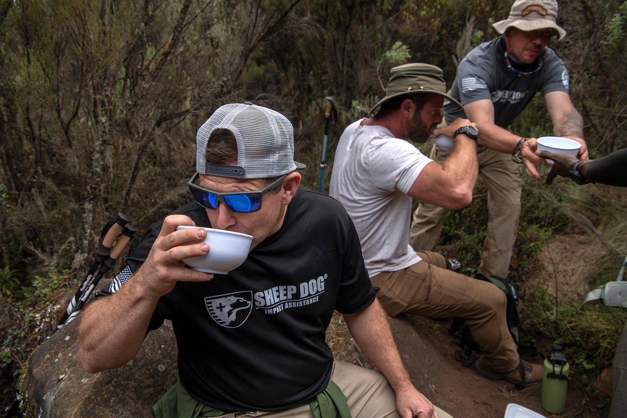 Michael Nimmo (left) and Noah Galloway sip on their soup as the guides hand Chris MacKay his bowl for lunch on August 5, 2021 during day two of the eight-day climb to summit Mount Kilimanjaro. Hot soup and porridge was a main staple of food throughout the trek as well as consuming four to six litters of water a day.